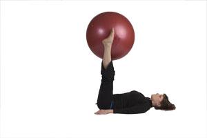 Contracción abdominal con bola grande extendiendo las pierna