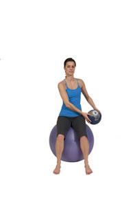 Diagonales Heben eines Medizinballes auf dem Gymnastikball