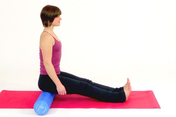 Oberschenkeldehnung sitzend mit Pilates Roller